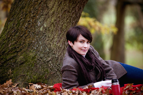 Beautiful woman with short, brown hair in pants and brown jacket lying in front of tree with leaves, fall setting